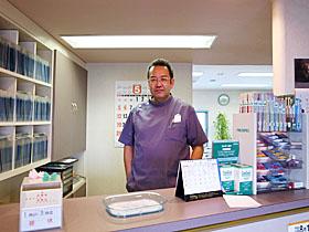 画像:受付に立つ鈴木院長